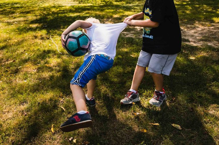 little boys play soccer with each other in their backyard, grabbing each other roughly