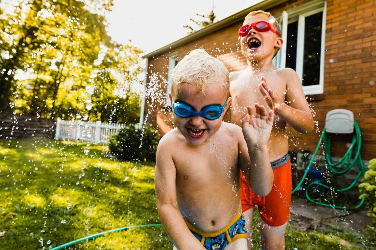two boys playing in the sprinkler in the backyard