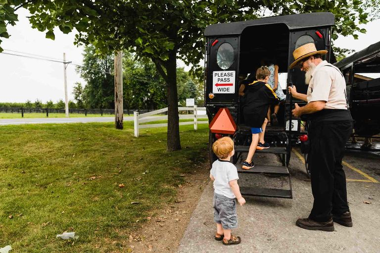toddler hesitates to enter an amish buggy
