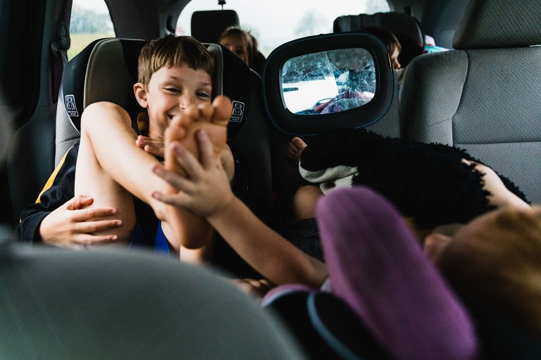 kids playing together in the car, hand on foot