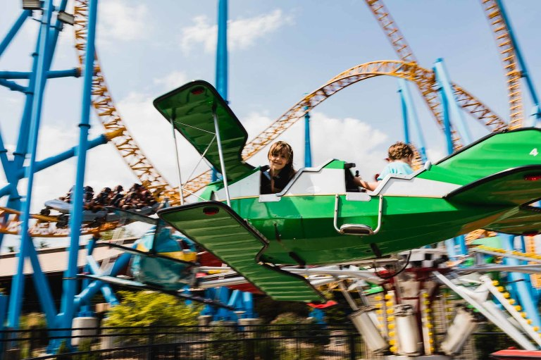 little girl in airplane ride looks down at photographer, surrounded by roller coaster at hershey park