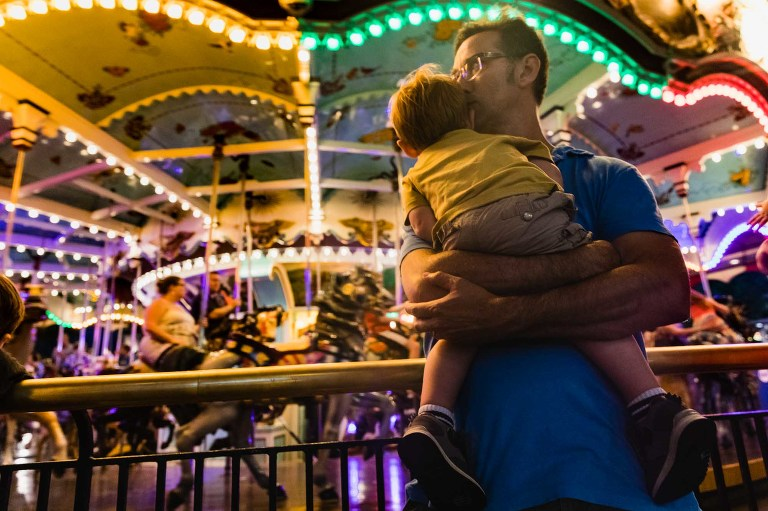 dad holding tired toddler closely in front of the carousel, late at night