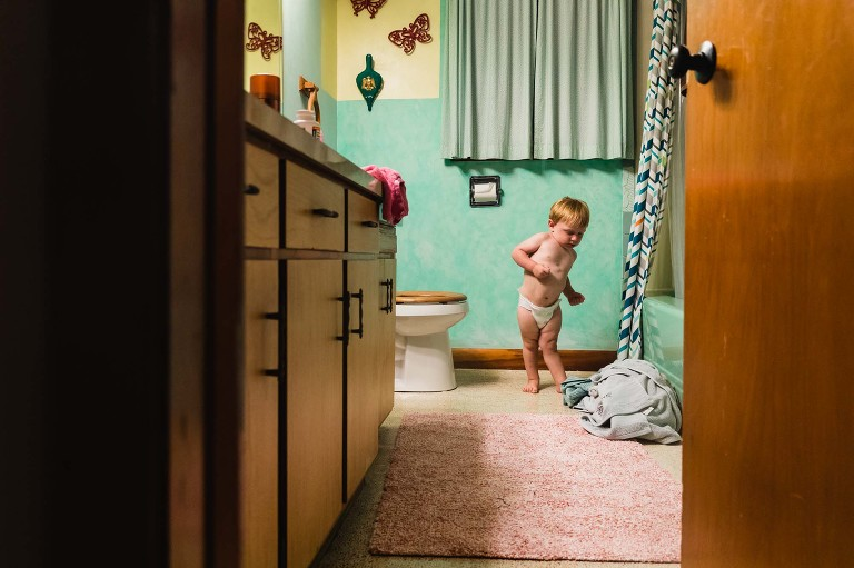 toddler in diaper standing next to toilet twisting his body up as he tries to poop