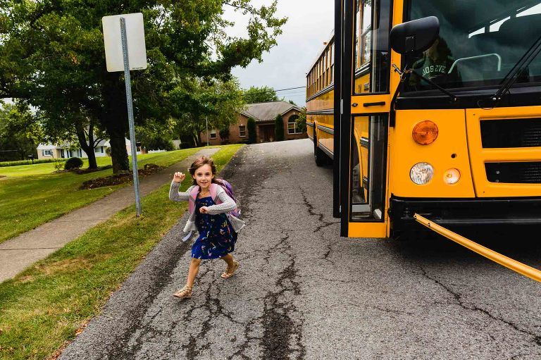 girl running off bus excitedly