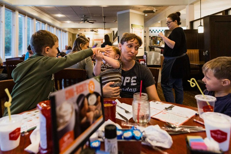 family eating in restaurant, mom holding baby and talking to boy while another boy plays with toddler