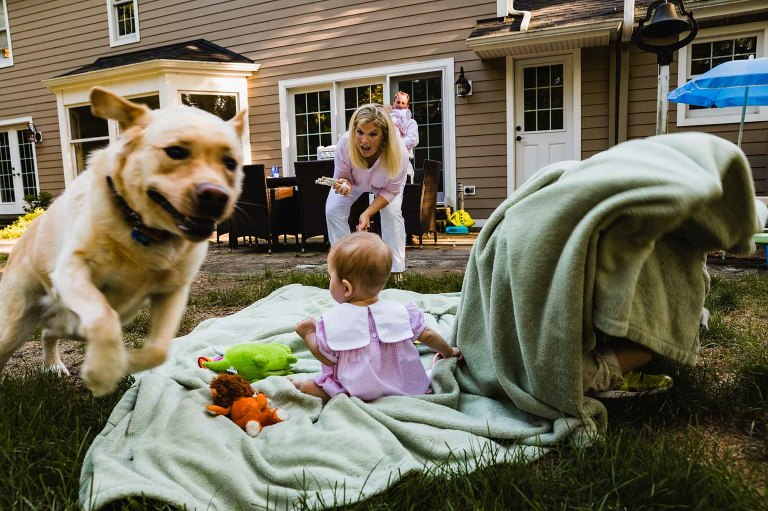 dog runs away from mom and baby sitting on blanket, with mom yelling at him