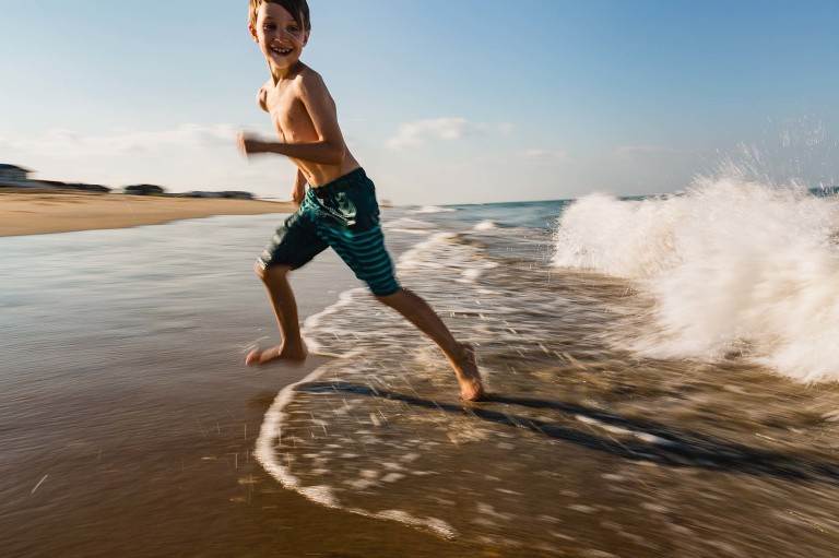 boy running away from waves at the beach
