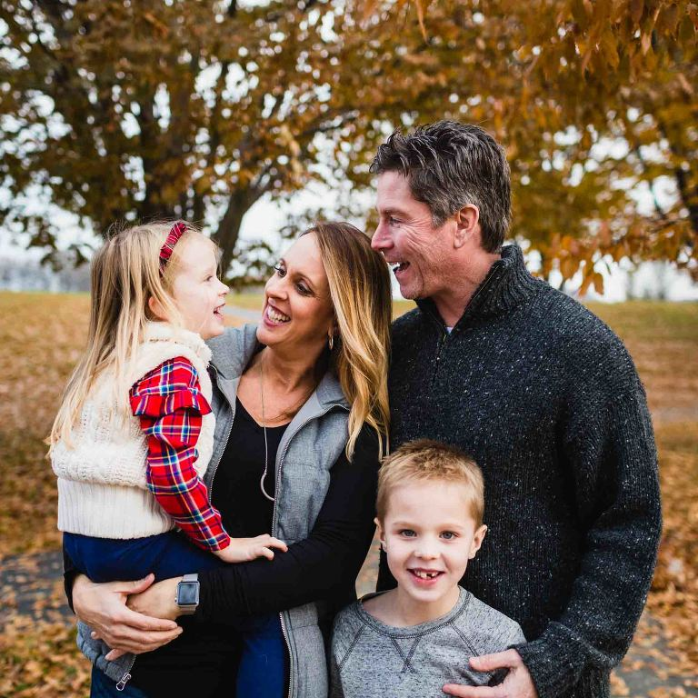 fun family photo outside in fall, dad and mom laughing with little girl mom is holding. other boy standing and smiling at the camera