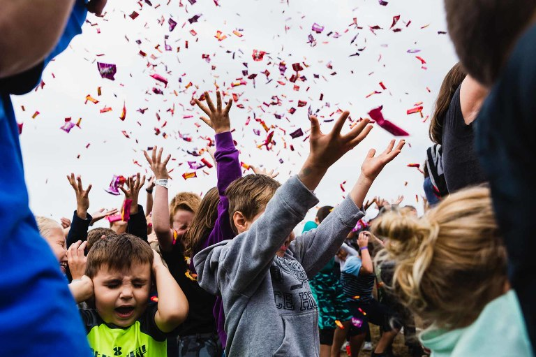 candy falling down on kids, with arms outstretched