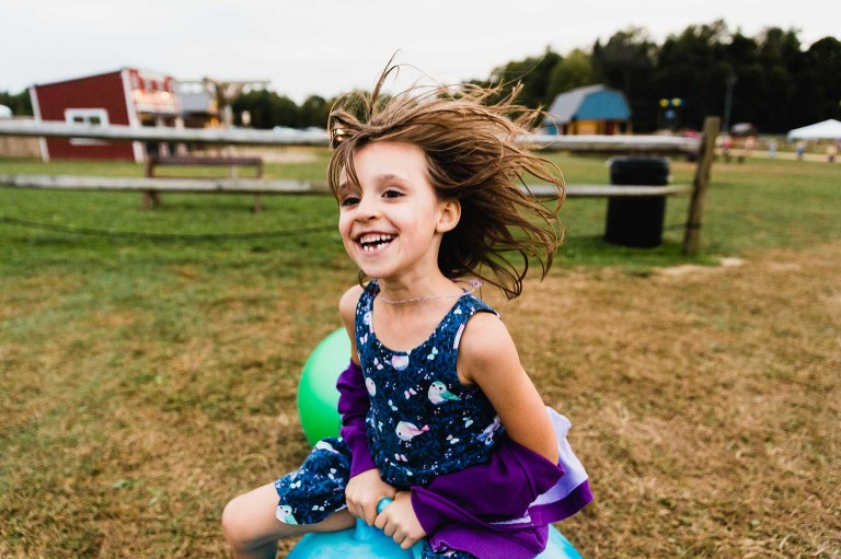 smiling girl bouncing on ball with hair flying