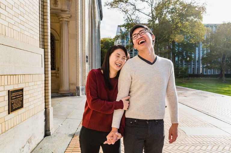 boy and girl holding hands, walking, and laughing together on carnegie mellon's campus