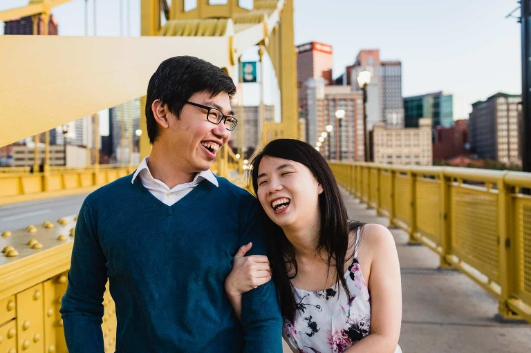 asian couple laugh together joyfully, framed by yellow bridge and city of pittsburgh