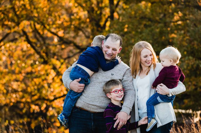 mom, dad, and their three boys snuggling together in front of warm fall foliage at sunset