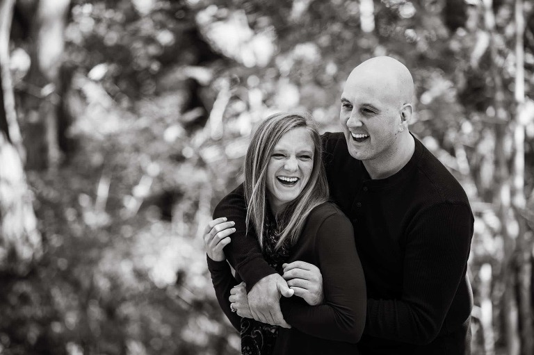 closeup black and white photo of man and woman laughing together, his arms around her