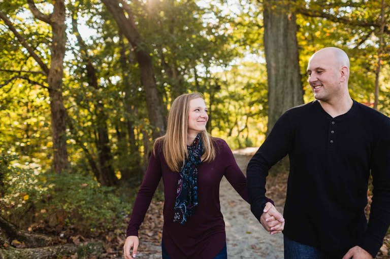 woman and man holding hands and walking a path in the woods, smiling at each other