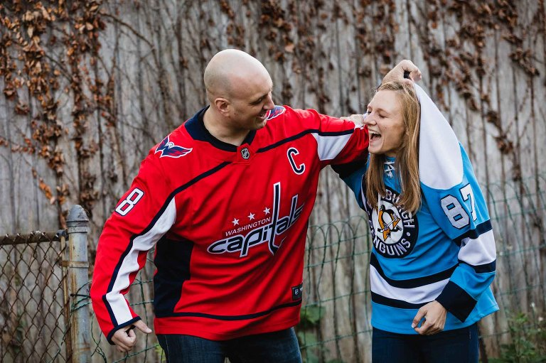 man in capitals jersey pretending to beat woman in penguins jersey, laughing