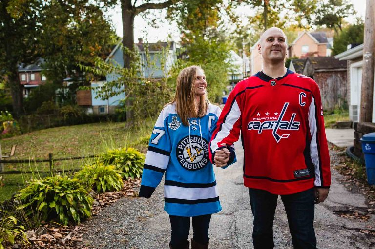 woman in penguins jersey and man in capitals jersey walking together smiling hand in hand