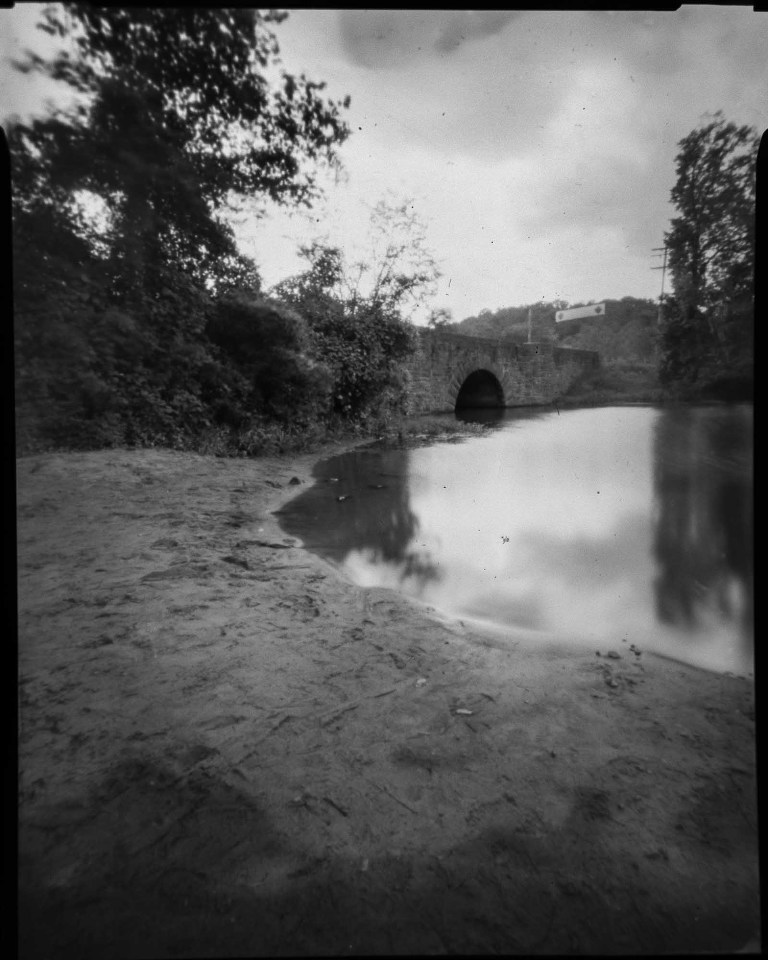 black and white ethereal pinhole photograph of bridge by a lake