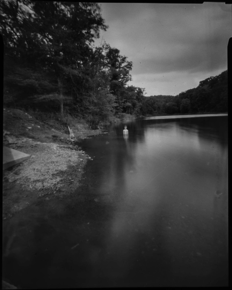 black and white ethereal pinhole photograph of figure coming out of the water