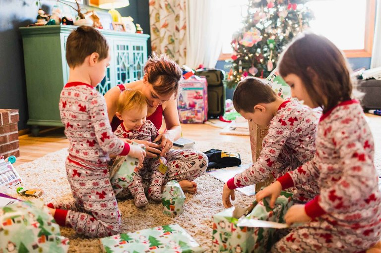 kids and mom opening gifts together on christmas morning
