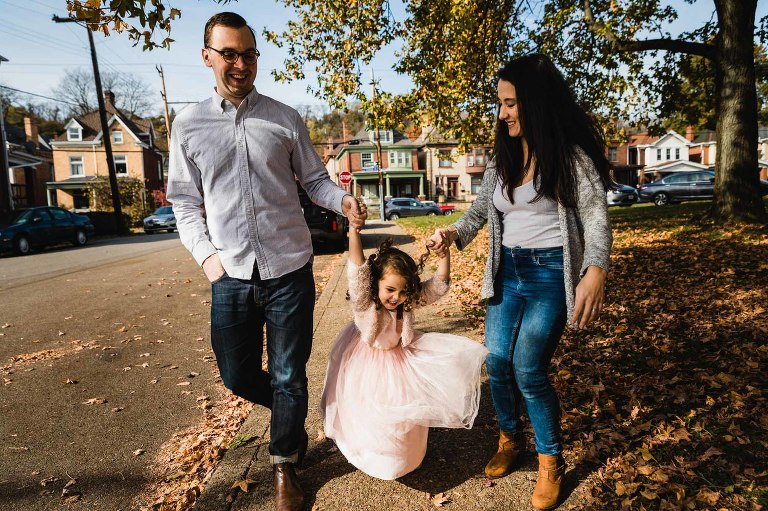 little girl in pink dress jumping and hanging on her parents' arms, walking down their city sidewalk