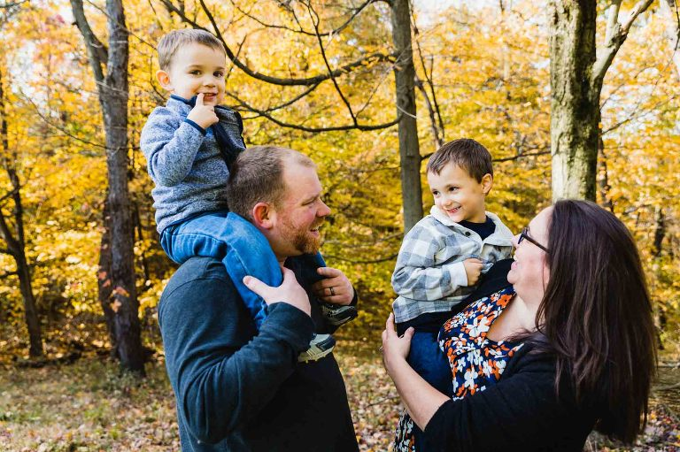 toddler on dad's shoulders, boy in mom's arms, all laughing together and looking at each other, in front of fall foliage