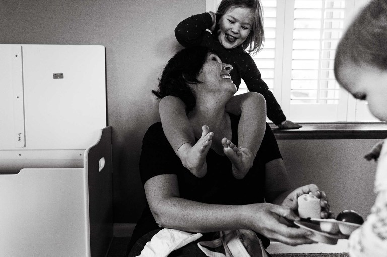candid black and white photo of mom looking up at her daughter sitting on her shoulders, laughing together