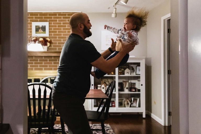 dad tossing toddler in the air. baby has scared expression and hair flying around