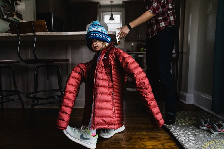 little girl dressed in her mom's giant oversized coat, shoes, and hat walks across the room.
