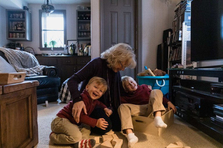 grandma wrestles with two boys on the floor of her home