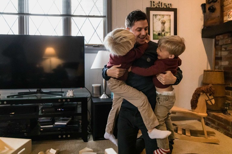 dad holds two wriggling boys laughing in his arms, wrestling on the floor