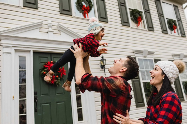 dad throws baby into the air, and mom holds dad from behind also laughing. house in the background.