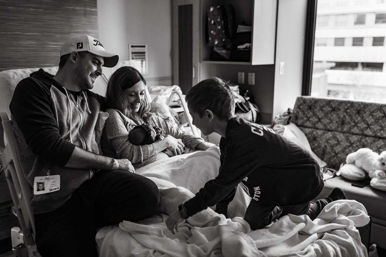 black and white photo of boy climbing up onto hospital bed to join his parents and new baby sister