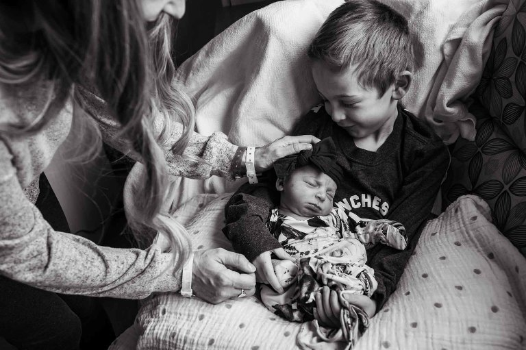 big brother holds baby sister, smiling, while mom reaches in