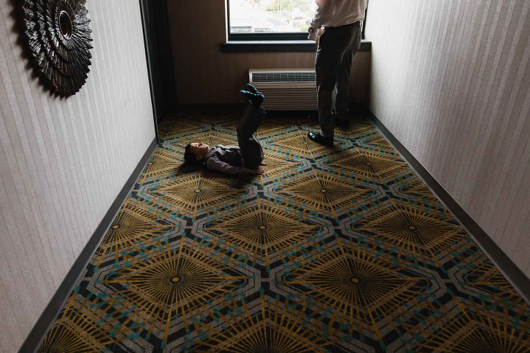 little boy lies on the ground in a hotel hallway, kicking his feet in the air
