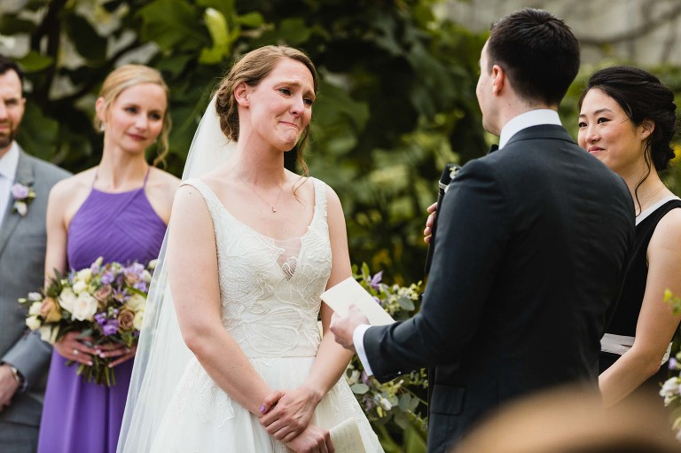 bride holds back tears during wedding ceremony, surrounded by family at phipps conservatory