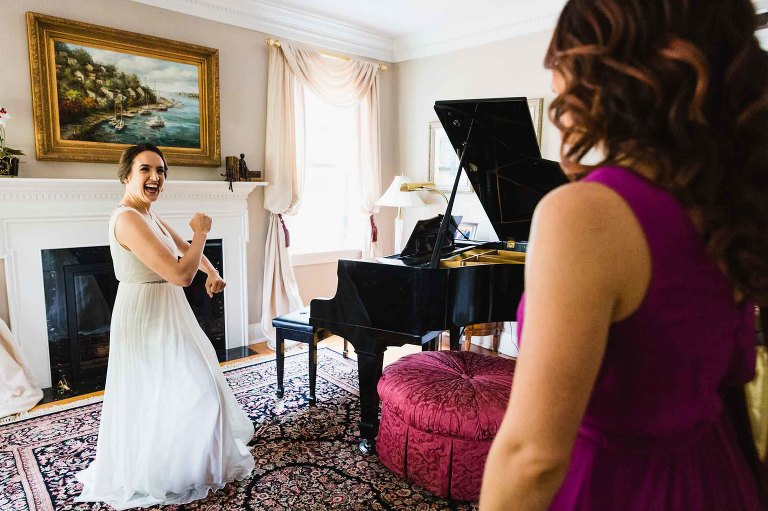 bride dances in front of elegant painting and piano, for her bridesmaids watching her
