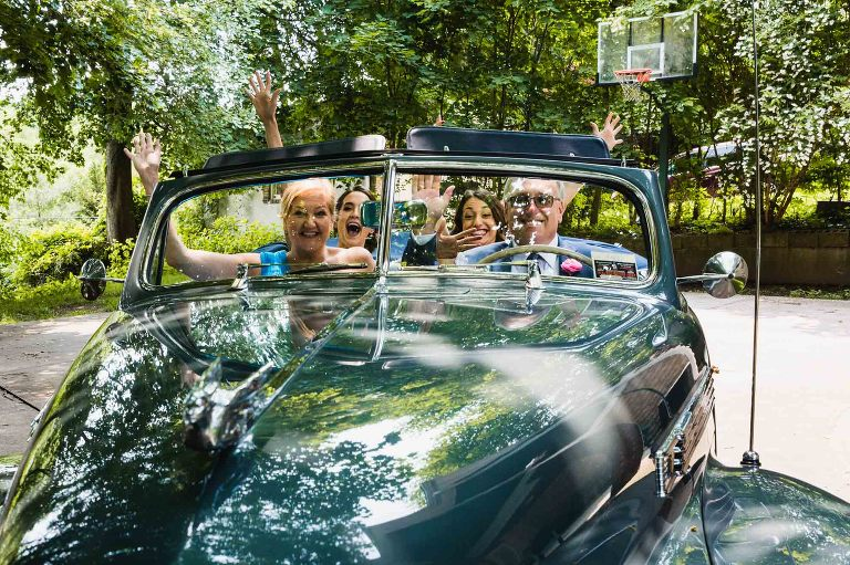 family cheering for the camera, seated in an antique jaguar car, in front of a basketball hoop