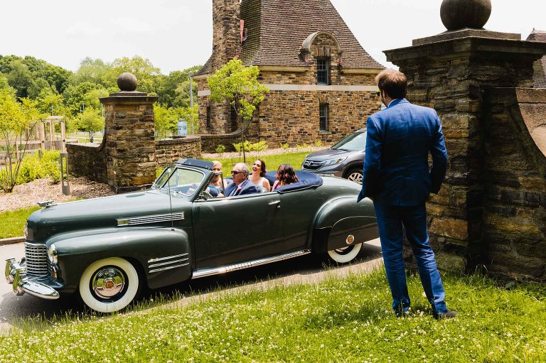 bride rides in an antique jaguar car with her parents, waving to her groom standing nearby