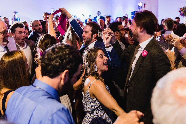 bride and groom dance wildly with their guests, as part of the greek money dance