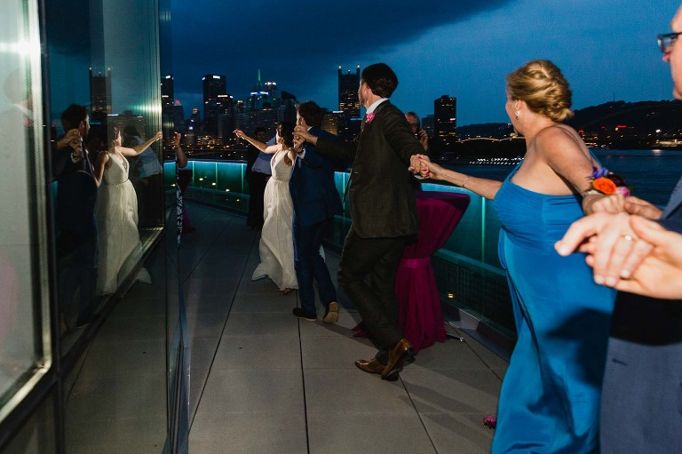 bride leads a train of wedding guests outside onto the patio at night, overlooking the city