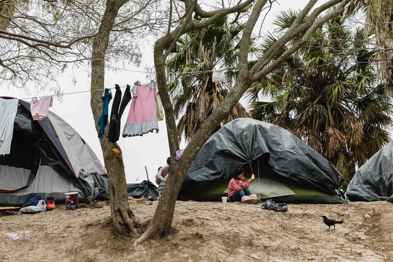girl eats bread, crow watches, clothing hanging from trees around her, in front of a refugee tent in matamoros