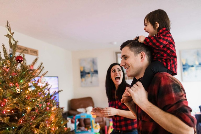 family decorates christmas tree together, baby girl sitting on dad's shoulders while mom laughs
