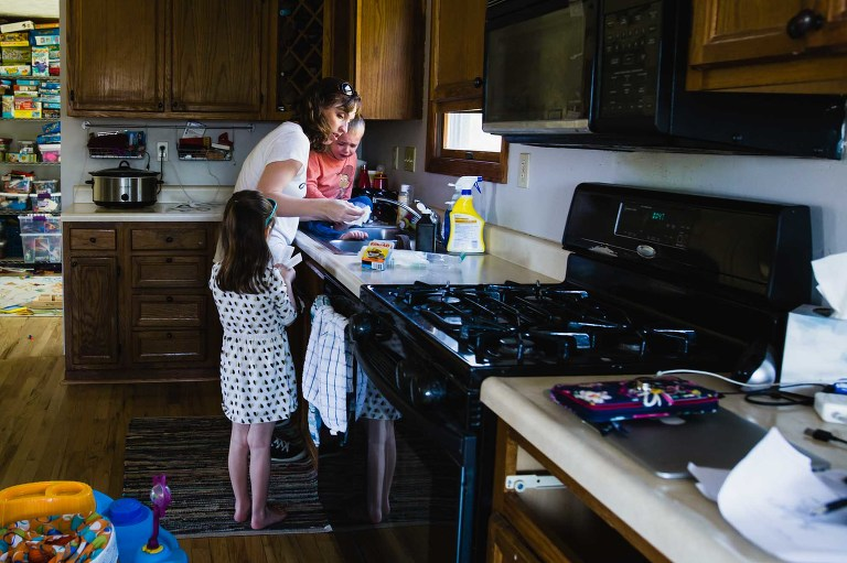 mom cleans out injury / boo boo with child in kitchen sink, while little girl hands up bandaids