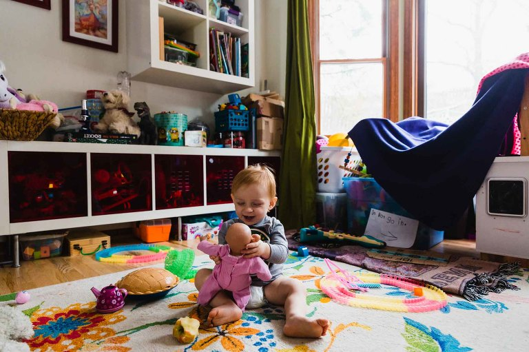 toddler plays with baby doll, sitting on the floor of a messy play room