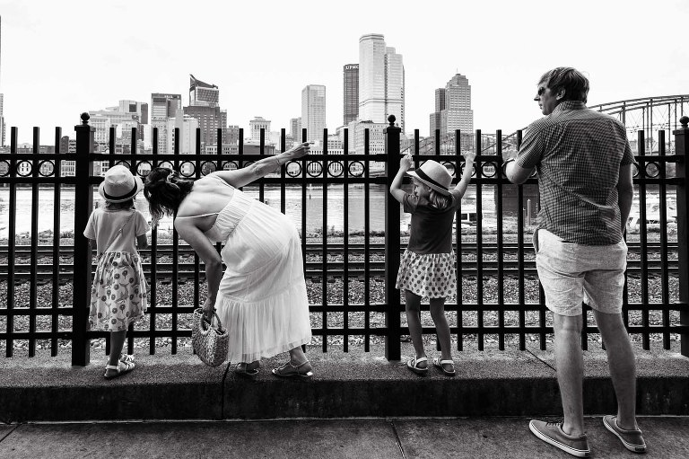 family stands in front of fence overlooking the big city of pittsburgh in the distance