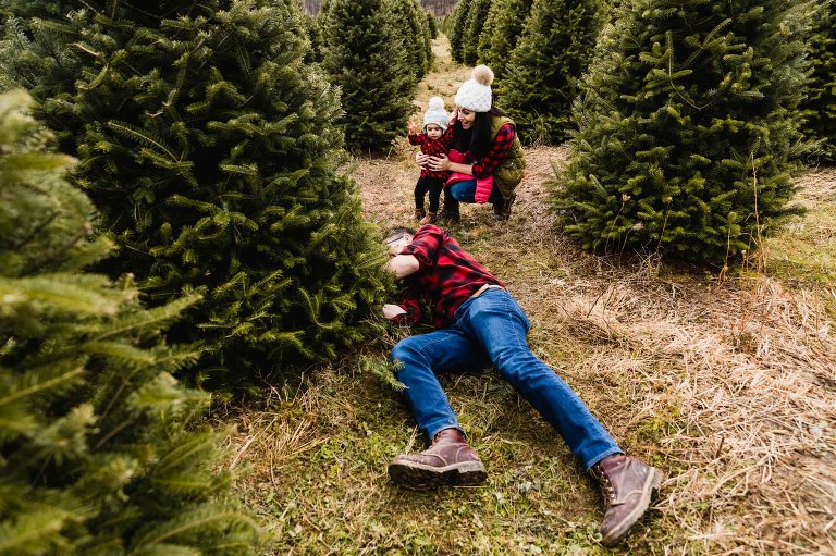 small family cuts down christmas tree together while little girl watches