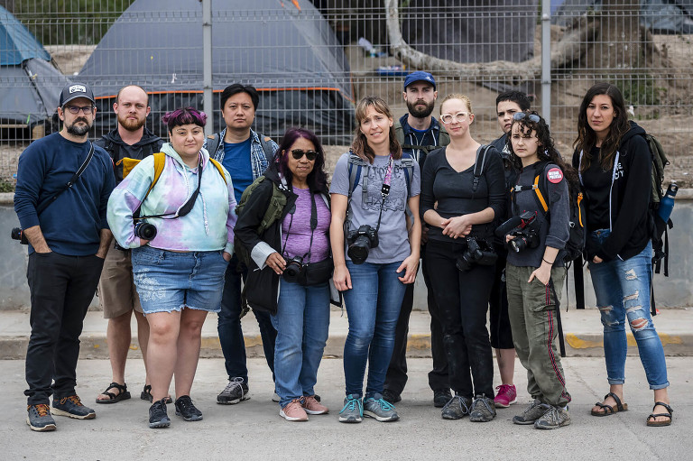 group of photographers, unsmiling, standing in front of a refugee camp in matamoros mx
