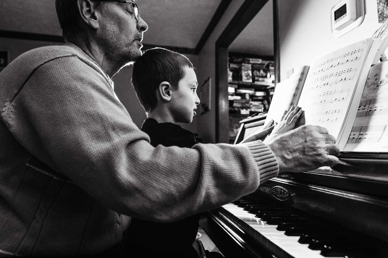 black and white photo of man playing piano with his grandson sitting on his lap