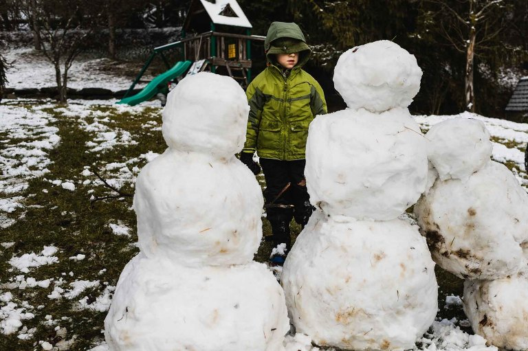 boy bundled up for winter weather, eyes hidden by his coat hood, standing in front of and looking at three snowmen.